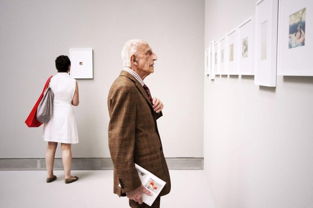 """Sono orgogliosa di questo scatto, non solo perché ha vinto il premio di migliore fotografia alla Biennale d'Arte 2011, ma perché conferma una cosa in cui credo molto. Sono fatalista e mi piace leggere 'segnali' nei fatti della quotidianità. Credo poi che se 'vuoi' puoi veicolare tutte le energie per raggiungere il tuo scopo. Desideravo da tempo fare un ritratto a Dorfles, così quando il Corriere mi ha chiesto di seguire la sua visita alla Biennale 2011 ho accettato con gioia. Dorfles è un incanto. Energia, vitalità, lucidità intellettuale. La conferma che l'arte salva l'uomo e allunga la vita. Stargli dietro, insieme ai colleghi che ne seguivano la visita, era complicatissimo. Camminava svelto, si fermava davanti a un'opera sempre circondato da un sacco di persone. Ogni tanto mi osservava e mi diceva :""""signorina che fa? Mi fa uscire brutto sul Corriere?"""" , deliziosamente vanitoso. Ad un certo punto il miracolo. Mi trovo da sola con la mia macchina nella sala dedicata a Ghirri, vuota salvo la presenza di una visitatrice che mi sta dando le spalle. Aggiustando l'obiettivo mi dico: """" Che bello se Gillo fosse qui ora"""". Alzo lo sguardo e lui è lì, come materializzato. Si avvicina ad una foto di Ghirri proprio davanti a me, aggiustandosi appena il nodo della cravatta. Scatto. Si avvera il sogno."""