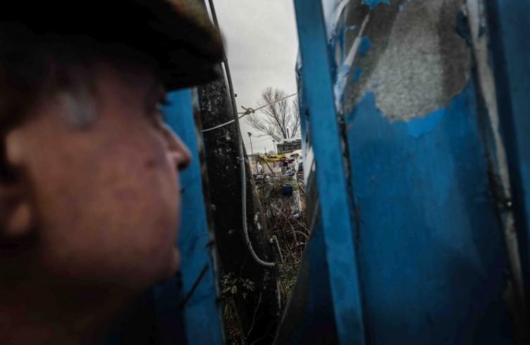 Via della Cupola, il proprietario di un terreno adibito a deposito guarda attraverso la recinzione dopo che un gruppo di rumeni ha occupato l'area, Inverno 2014