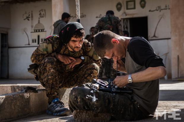 giovane volontario americano che ripara il fucile a un cecchino curdo- Mc Evoy Photo-